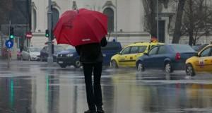 Fotografie simbol. Singur în ploaie, la protest, în faţa Guvernului